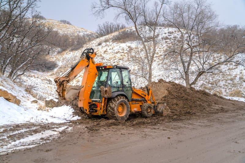 Backhoe lader tegen sneeuwheuvel en bomen stock afbeelding