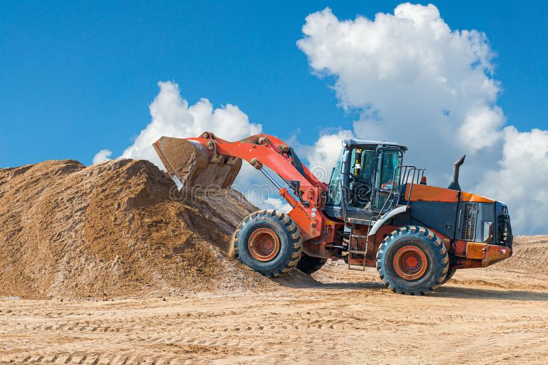 Backhoe loader or bulldozer - excavator with clipping path on a background with blue sky and clouds. work on construction site or. Sand pit, scoop, industry royalty free stock photo