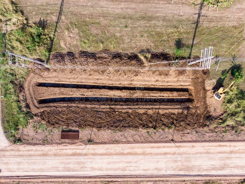 Backhoe loader digging furrow on estate land in countryside. Top view of backhoe loader digging furrow on estate land in countryside royalty free stock images