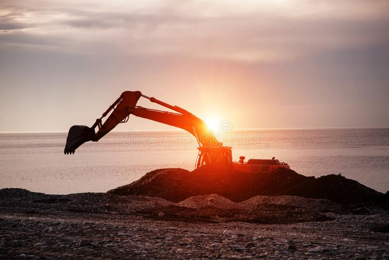 Backhoe o digger che lavora nel sito di scavo della terra immagini stock