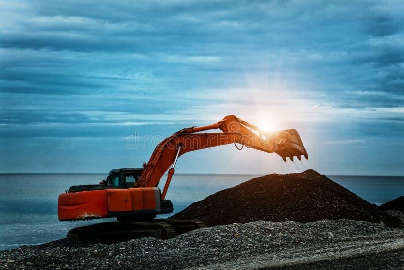 Backhoe o digger che lavora nel sito di scavo della terra fotografia stock