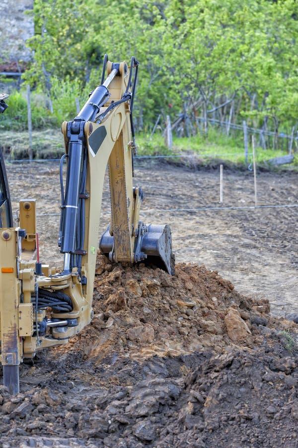 Backhoe opgravende aarde in een bouwwerf royalty-vrije stock foto