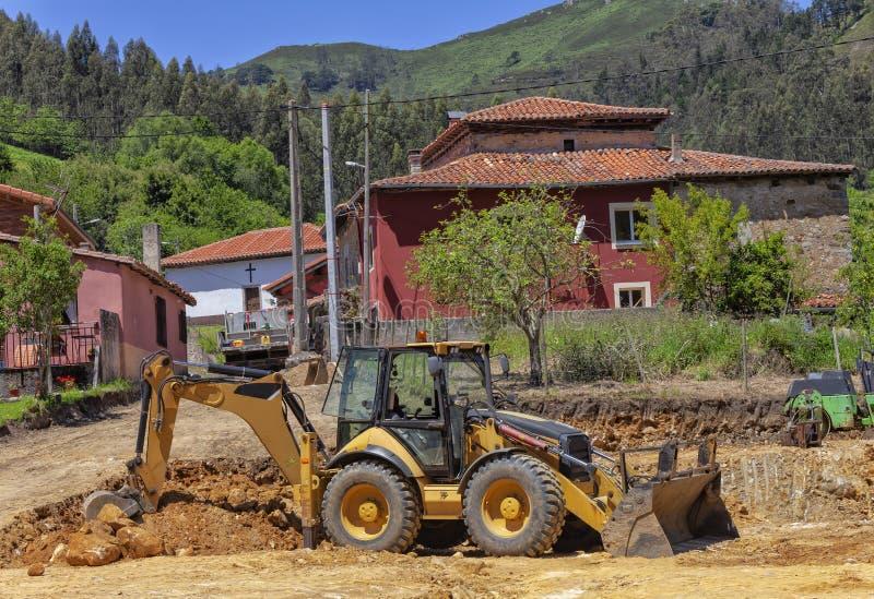 Backhoe opgravende aarde in een bouwwerf stock afbeelding