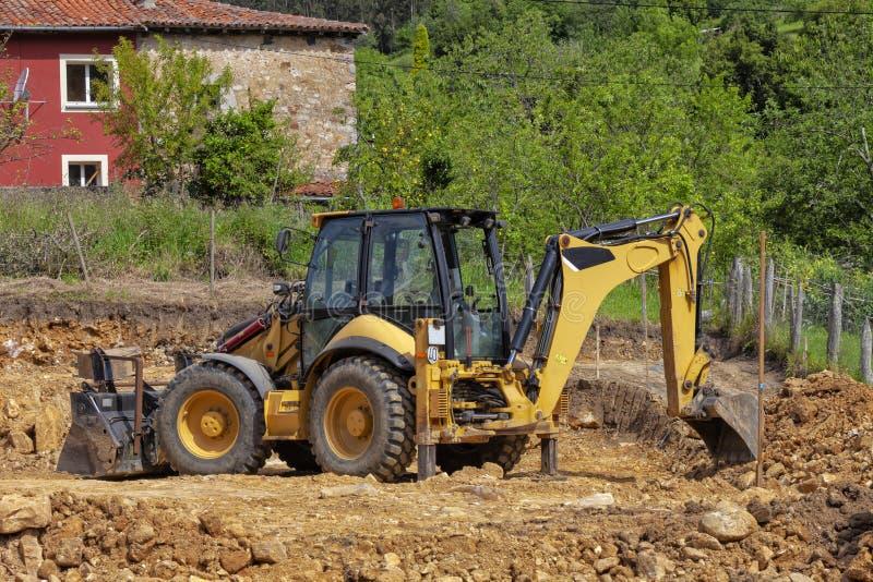 Backhoe opgravende aarde in een bouwwerf royalty-vrije stock foto's
