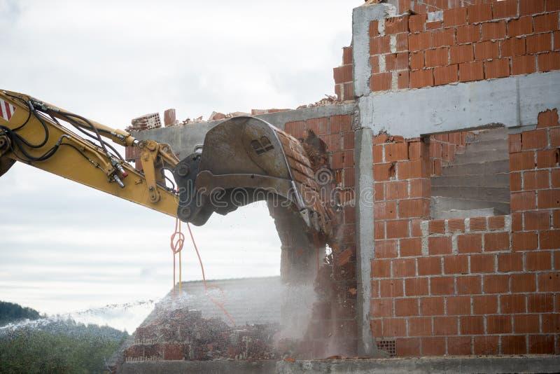 Backhoe que demole uma casa do tijolo imagens de stock royalty free