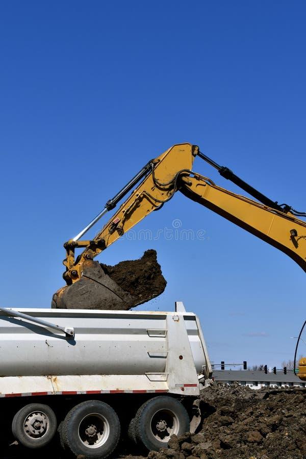 Backhoe stortplaatsenvuil in een vrachtwagendoos royalty-vrije stock afbeeldingen