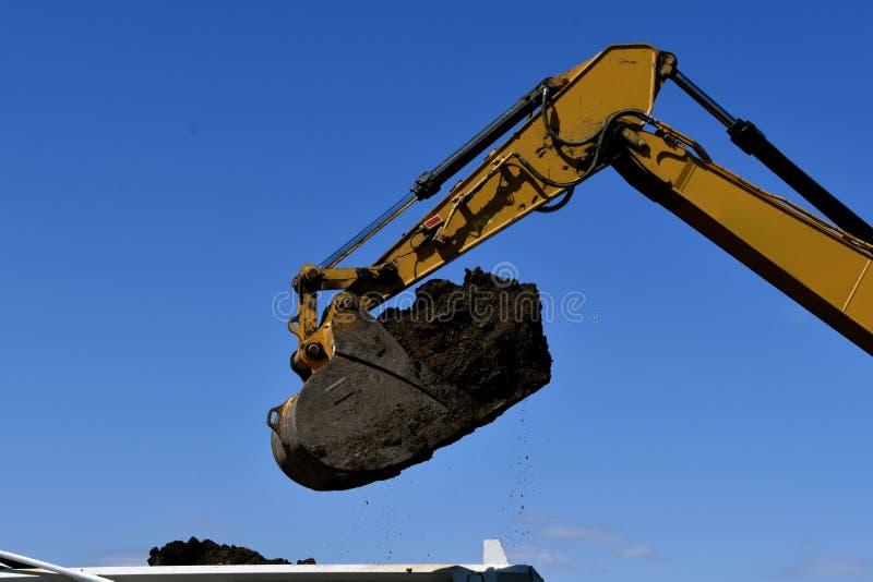 Backhoe stortplaatsenvuil in een vrachtwagendoos stock foto's