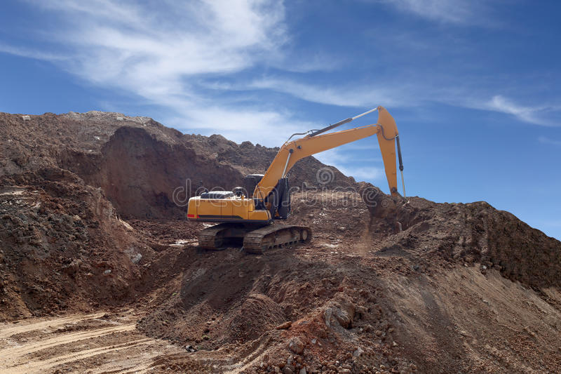 Backhoe was digging ground working and construction dam for Storing water. Backhoe was digging ground working and construction dam for Storing water,Blue sky royalty free stock photography