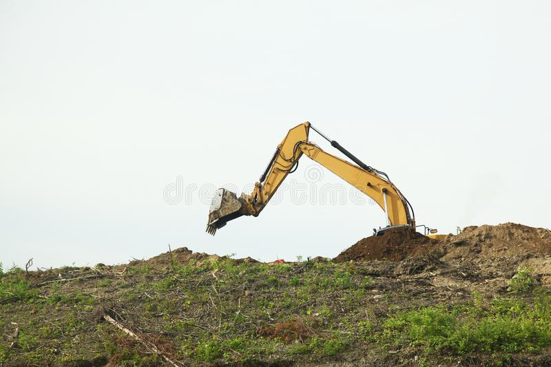 The backhoe was digging soil on top mountain stock photo