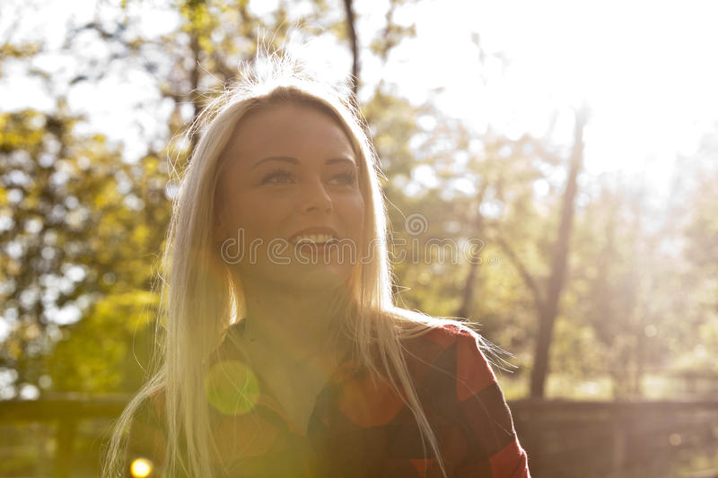 Backlight blonde woman in the park stock photography