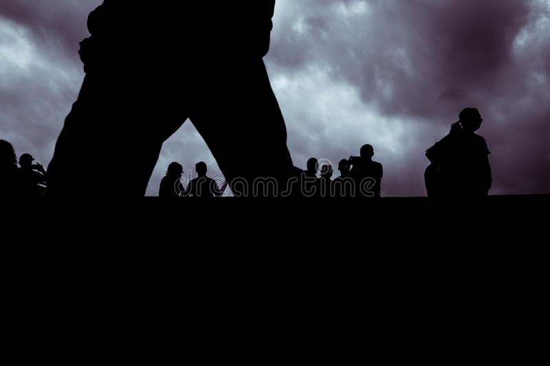 Backlight of a cloudy day with a silhouettes of a group of unrecognizable people royalty free stock image