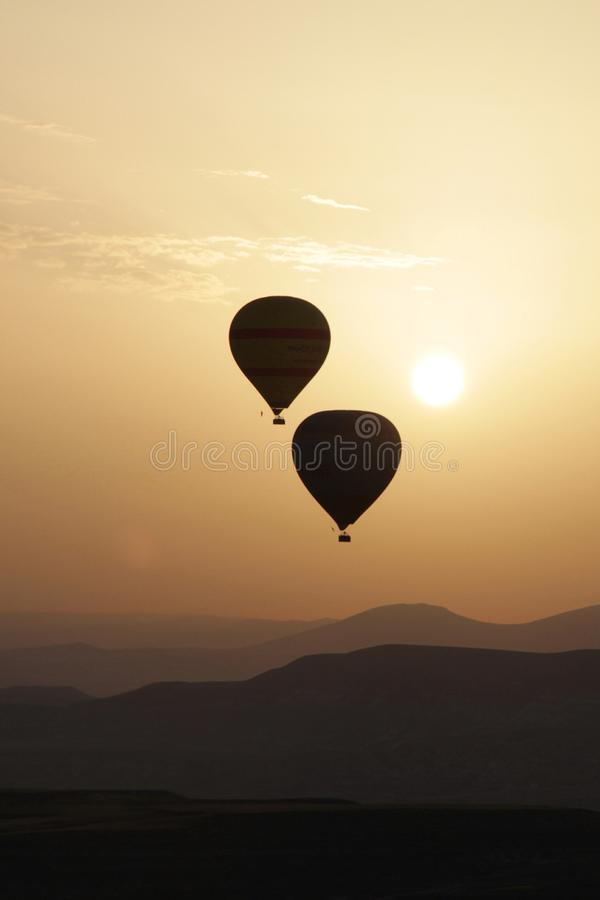 Wallpaper. Hot air balloons ata sunrise. Backlight image of two hot air balloons at sunrise. Photography suitable for mobile wallpaper.Ccolors in the image royalty free stock photo