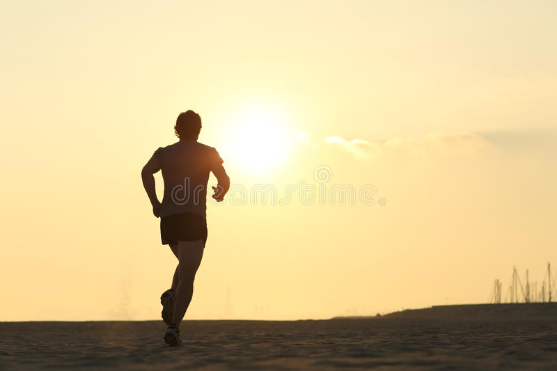 Backlight of a jogger running on the beach royalty free stock photo