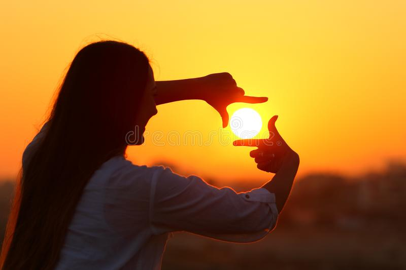 Woman framing sun with fingers at sunset. Backlight portrait of a woman silhouette framing sun with fingers at sunset stock photography