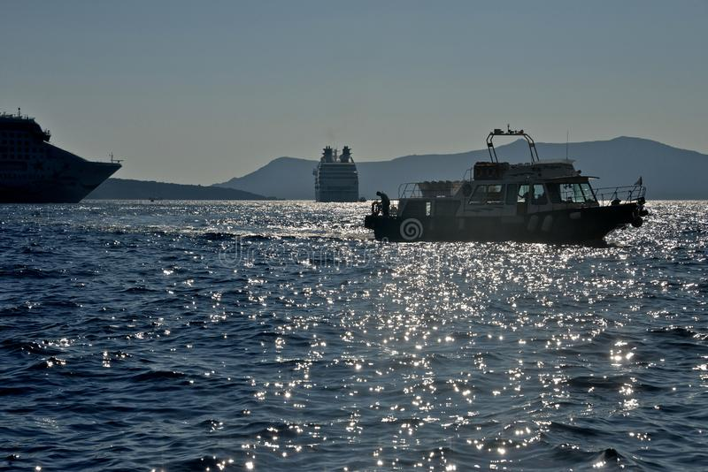 seascape with silhouette of boat and cruise ship anchored in Santorini stock image