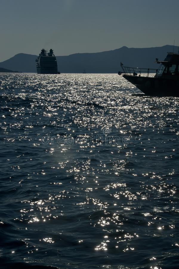 seascape with silhouette of boat and cruise ship anchored in Santorini stock photos
