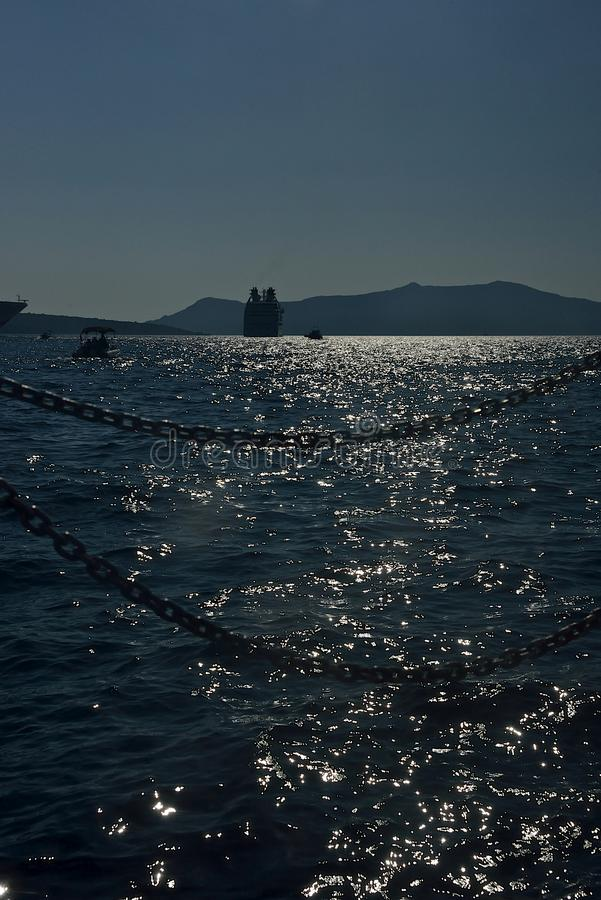 seascape with silhouette of boat and cruise ship anchored in Santorini stock photography