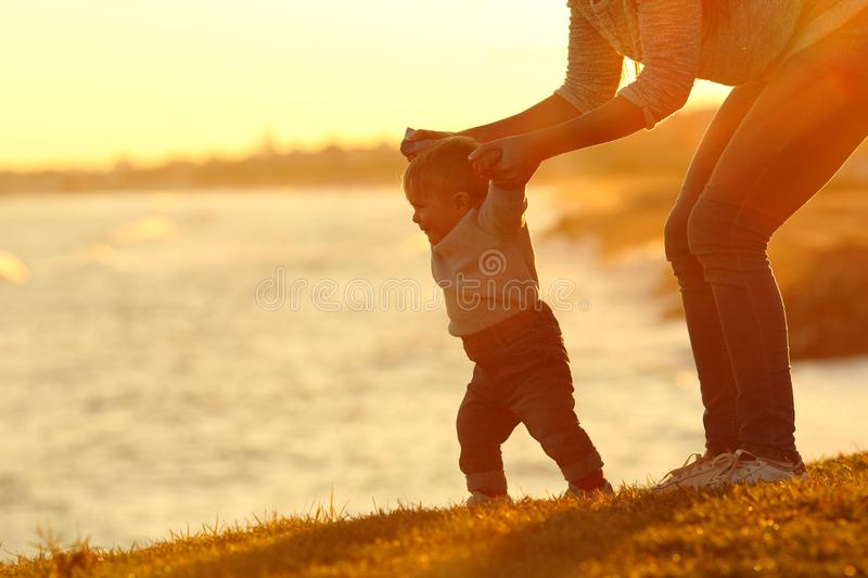 Confident baby learning to walk and mom helping him stock photos