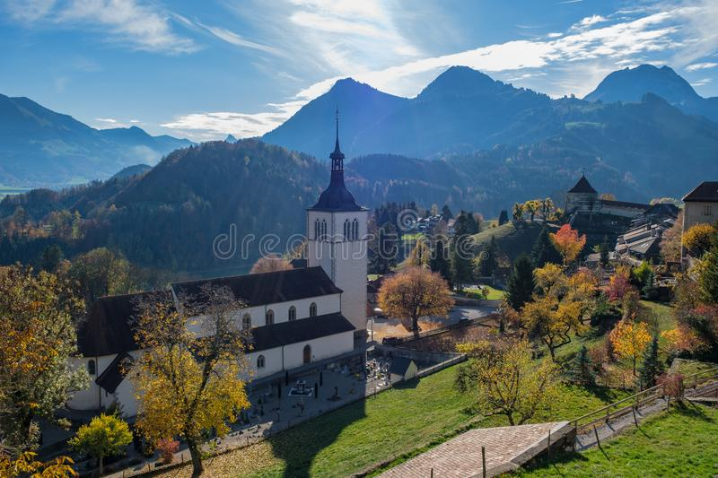 Backlight view with autumn light on the alps, church and cemetery in Gruyeres, Switzerland royalty free stock image