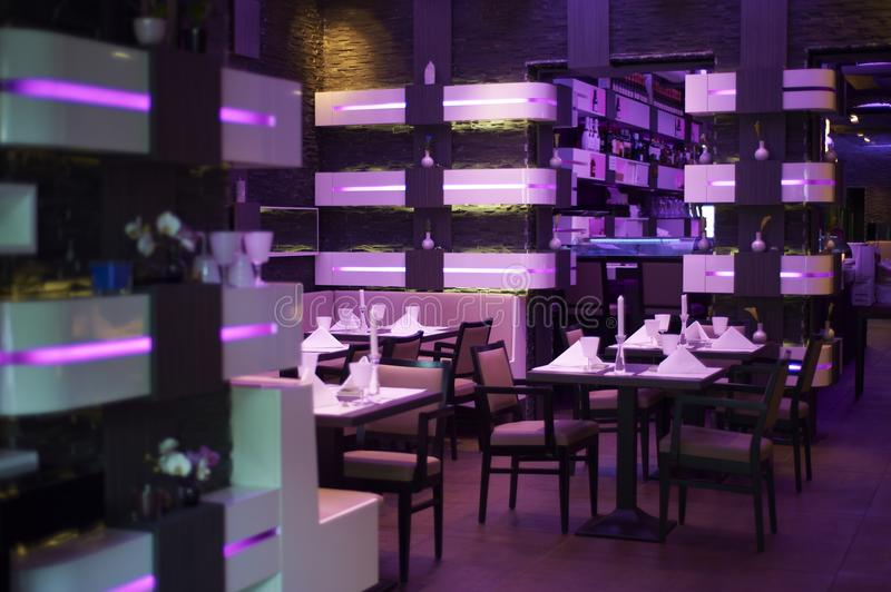 Backlighted modern restaurant. View inside a lilac backlighted modern restaurant with nice decoration on the tables stock photo