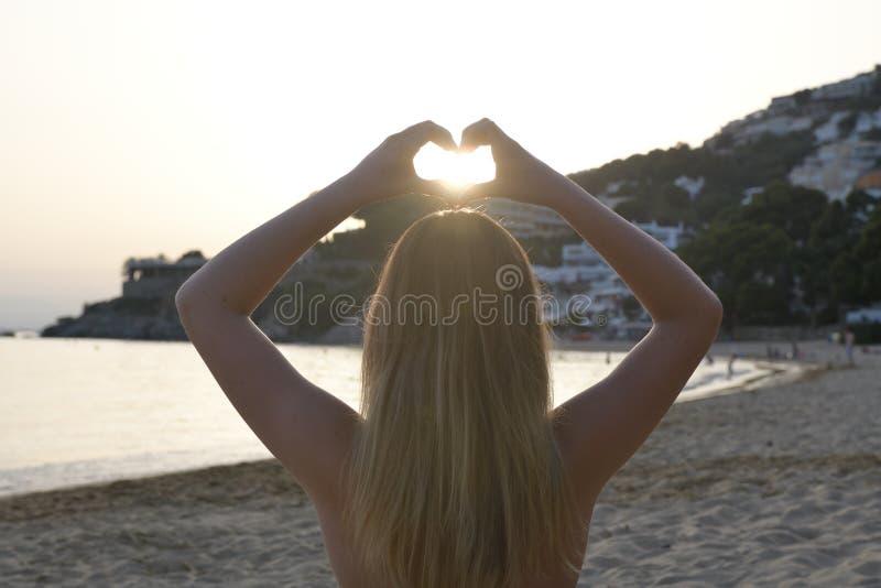 Backlighting a imagem de uma menina em uma posição da ioga de volta à câmera que faz uma forma do coração com suas mãos fotos de stock