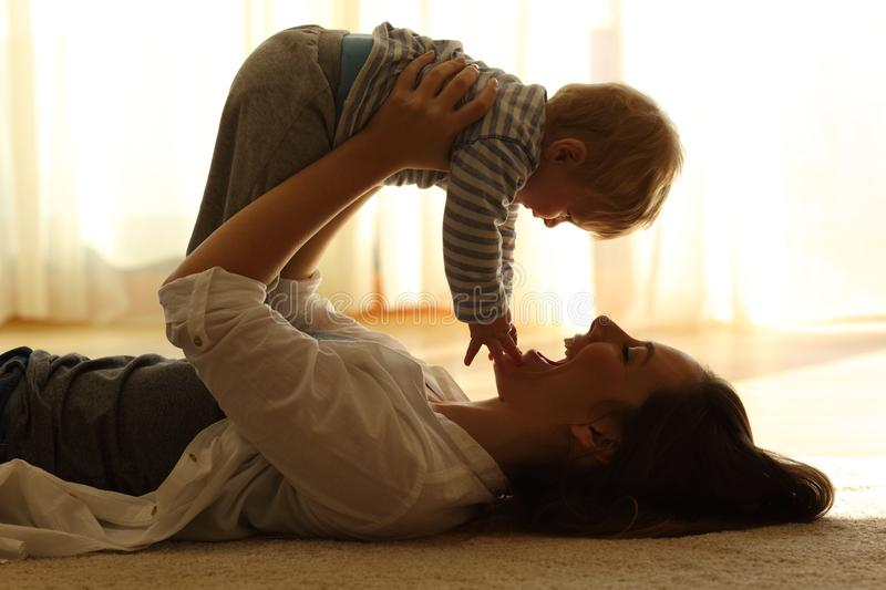 Backlighting of a mother raising her baby at home royalty free stock photo