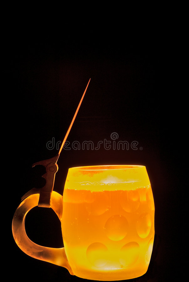 Backlit Beer Mug. Beer in a mug with back lighting. Taken in studio. Isolated on black background. Vertical format. Copy space available on top half of photo stock images