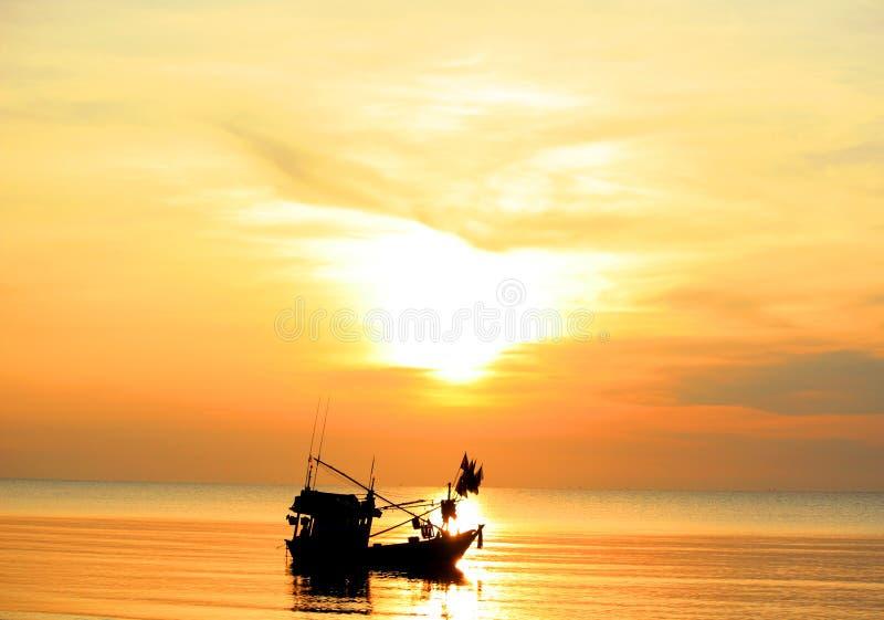 Backlit boat in the dawning ocean. One backlit boat in the dawning ocean, Thailand royalty free stock photo