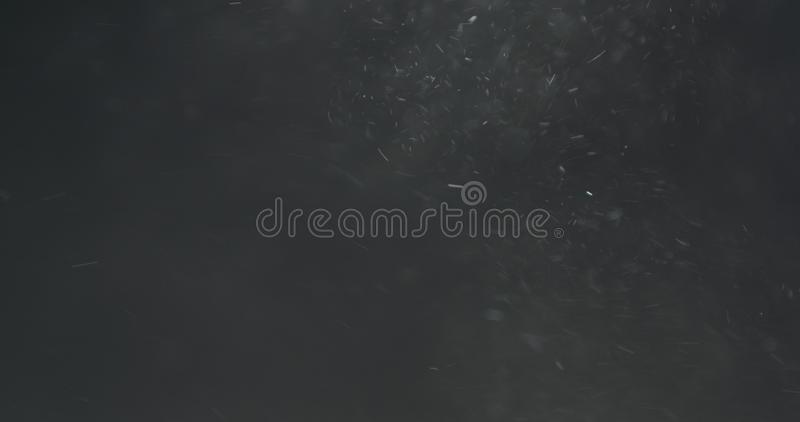 Backlit dust particles explosion effect on a black background with motion blur. Wide photo royalty free stock images