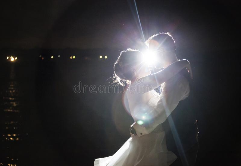 Backlit night wedding couple kissing royalty free stock photography