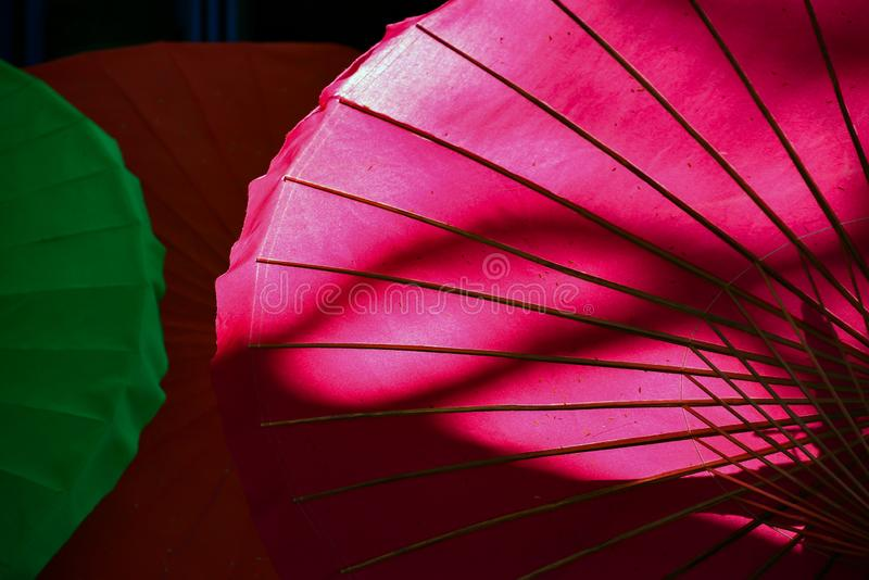 Backlit pink umbrella showing ribs and colour. Backlit bright pink umbrella featuring rib and frame outline against dark background royalty free stock image