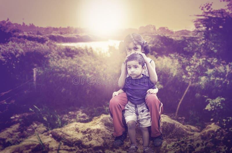 backlit portret brata siostrzany siedzący bawić się zdjęcie stock
