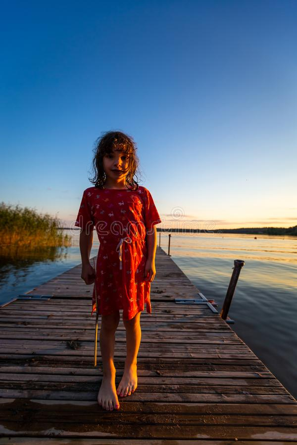 Backlit summer night portrait of a young caucasian girl in red dress on a jetty with water and blue sky. Vertical composition royalty free stock photography