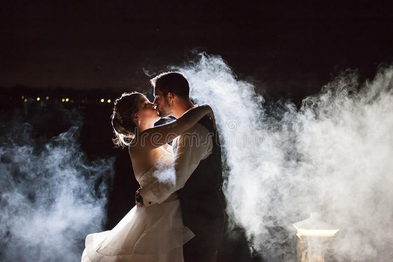Bride and Groom kissing in fog at night. A backlit wedding couple kissing on edge of river with smokey fog around them at night stock photos