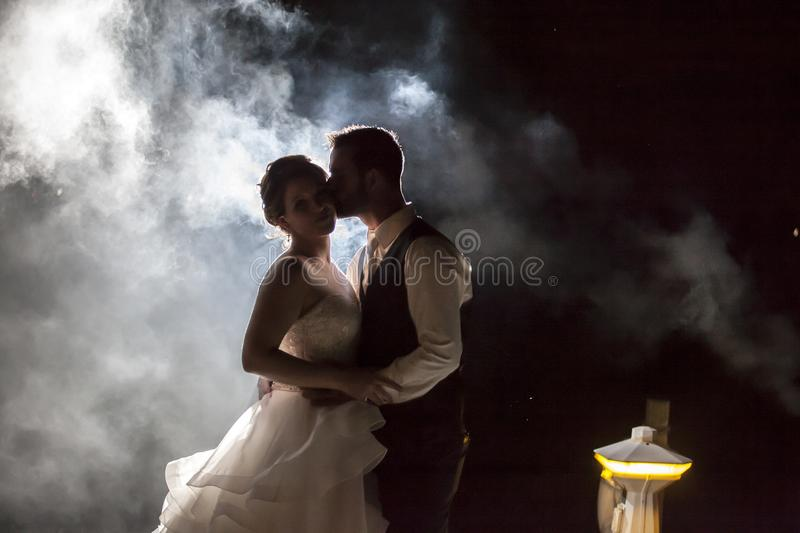 Bride and Groom kissing in fog at night on a dock stock photo