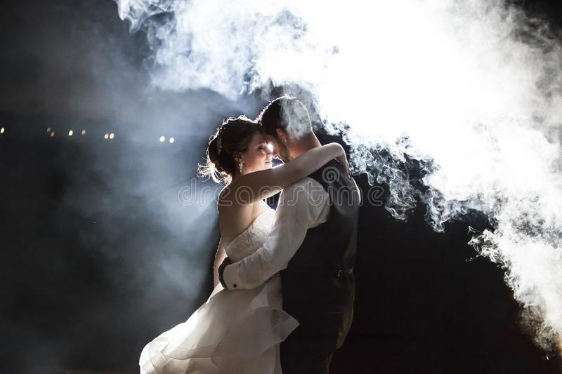 Bride and Groom under fog at night royalty free stock photo