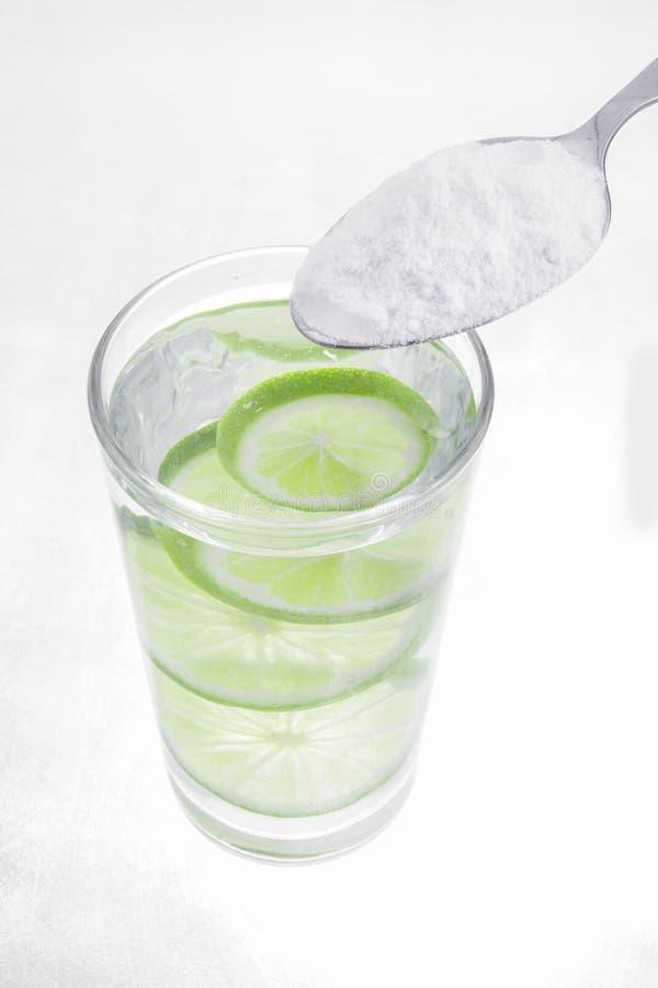 Backnatron, Zitrone und Glas Wasser lokalisiert auf weißem Hintergrund lizenzfreie stockfotografie