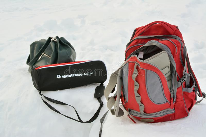 Backpack, bag, tripod in the snow. Preparing for video and photo shooting in the forest. stock photo