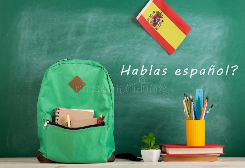 """backpack, blackboard with text """"hablas español"""", flag of the Spain, books and school supplies stock images"""