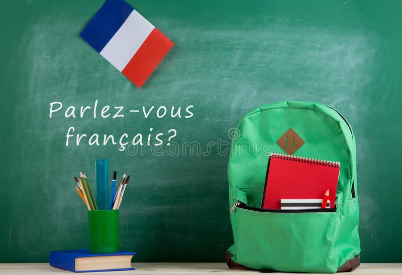 """backpack, blackboard with text """"parlez-vous français?"""", flag of the France, book and school supplies royalty free stock photo"""