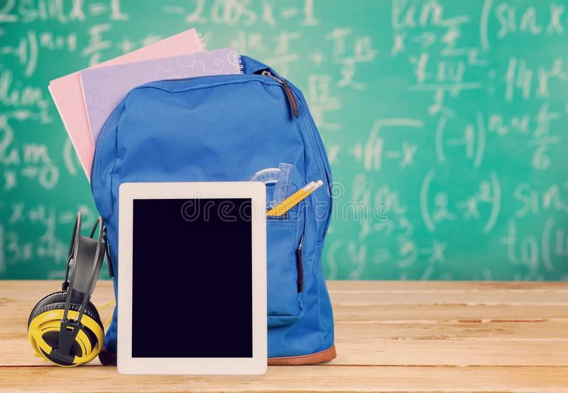 Backpack and digital tablet on the table royalty free stock images
