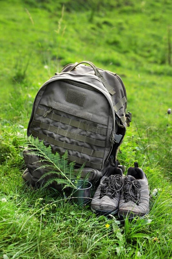 Backpack e facendo un'escursione gli stivali in valle verde della montagna immagine stock libera da diritti