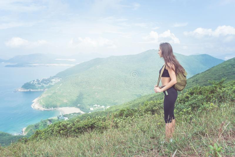 Backpack female traveler standing on hill looking at sea and mountains. Trail runner taking a break enjoying view of royalty free stock photo