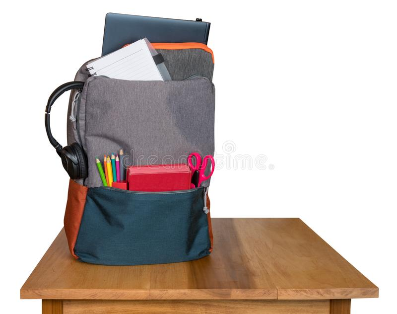Heavily loaded backpack with school supplies on wooden table and isolated royalty free stock image