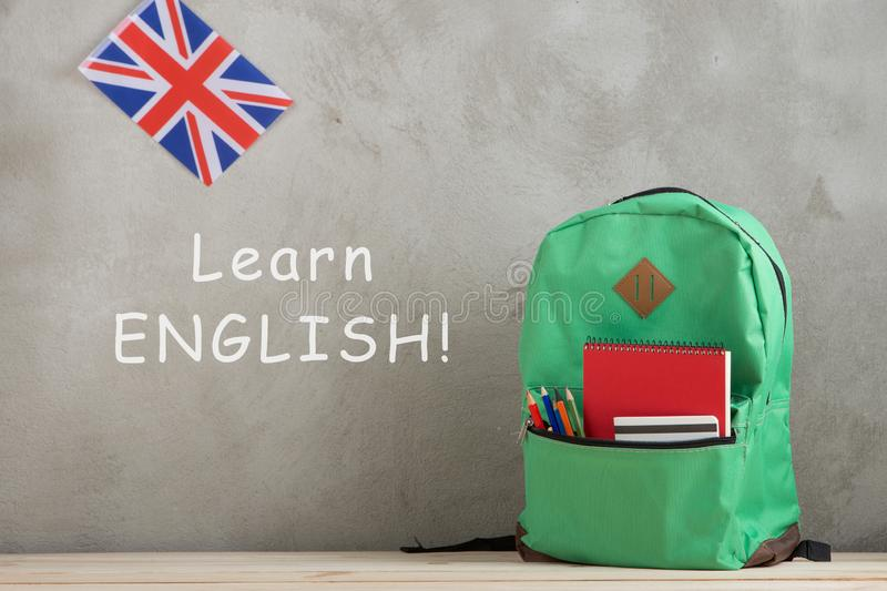"""backpack, flag of the Great Britain and notebooks against a cement wall with text """"Learn English royalty free stock images"""