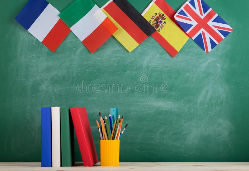 Backpack, flags of Spain, France, Great Britain and other countries, books and school supplies of the blackboard. Learning languages concept - flags of Spain royalty free stock photo