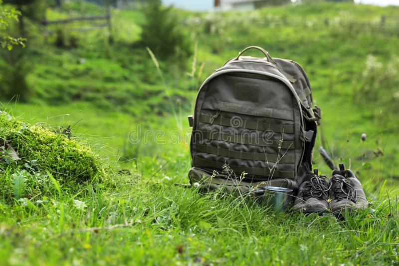 Backpack and hiking boots in green mountain valle royalty free stock photo
