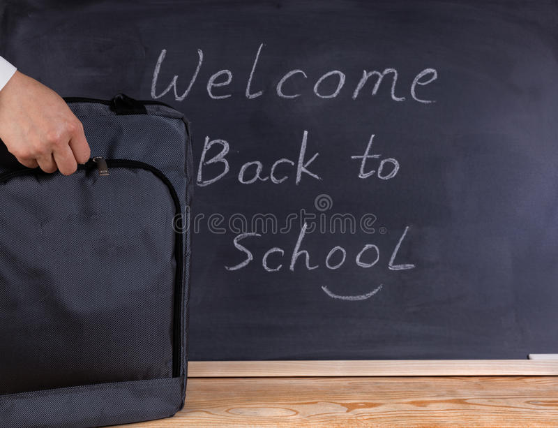 Backpack na classe com o quadro preto apagado no fundo foto de stock royalty free