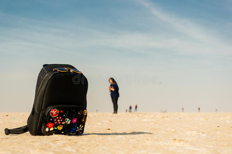 backpack placed on the white salt sand of the rann of kutchh with an indian girl standing in the distance stock photos