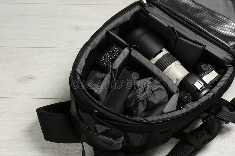 Backpack with professional photographer`s equipment. On wooden background royalty free stock photos